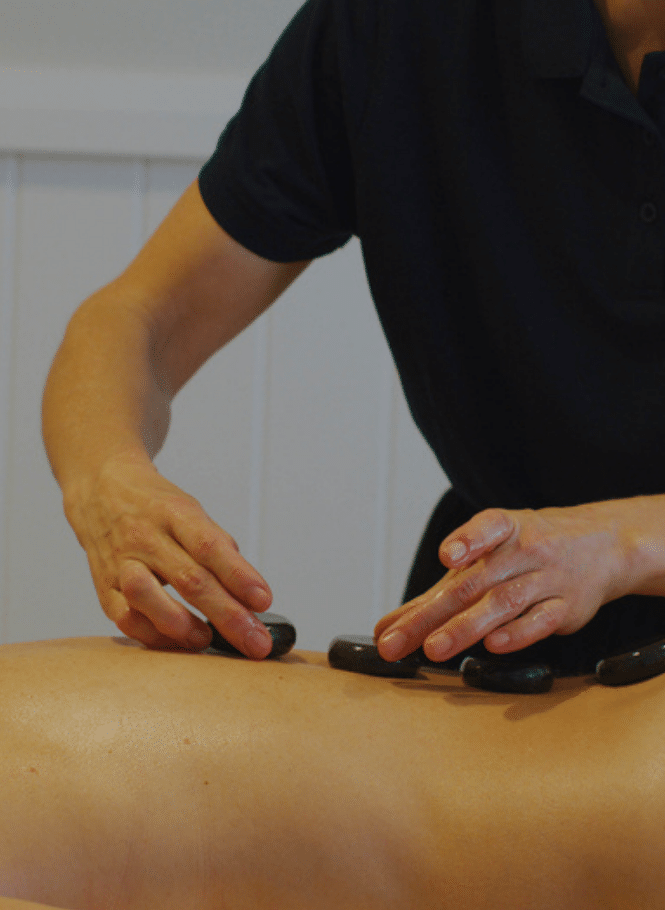 Massage therapist putting hot stones on guest's back