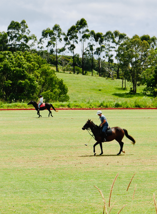 Two people riding horses on the Hazelwood Estate polo field