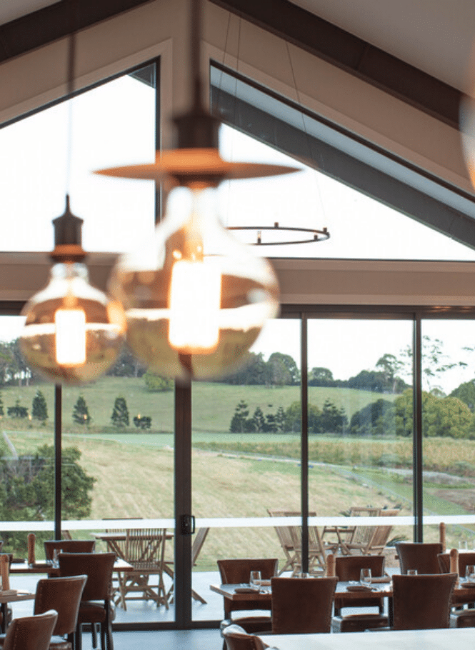Interior of The Paddock restaurant at Hazelwood Estate showing light features and Hinterland views